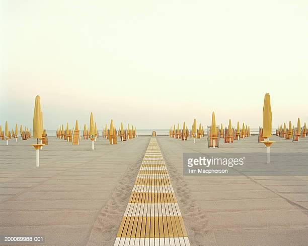 italy, rome, ostia, closed beach parasols and walkway - ombrellone da spiaggia foto e immagini stock