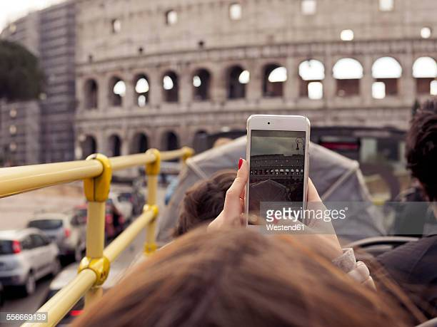 Italy, Rome, Tourists doing sightseeing tour in tour bus, passing Colosseum