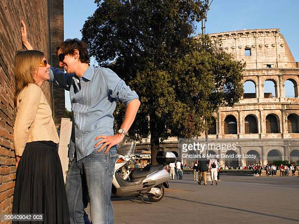 Italy, Rome, young couple talking, side view