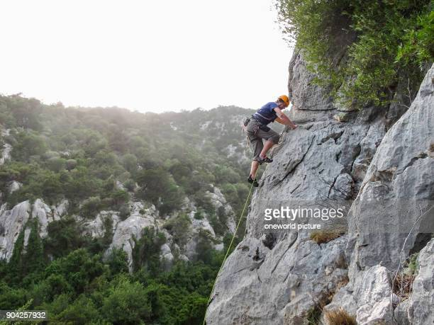 Italy Sardinia climber on steep limestone rock wall