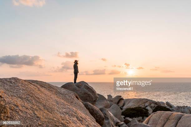 Italy, Sardinia, man standing on rock at sunset looking at view