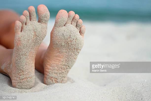 Italy, Sardinia, Woman lying on beach with sandy feet, close-up