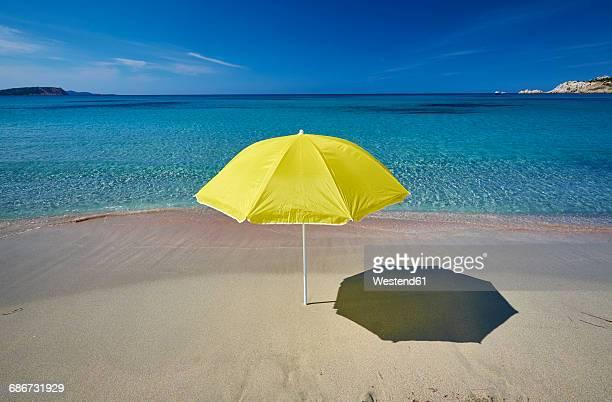 italy, sardinia, yellow sunshade on the beach at rena majori - parasol photos et images de collection