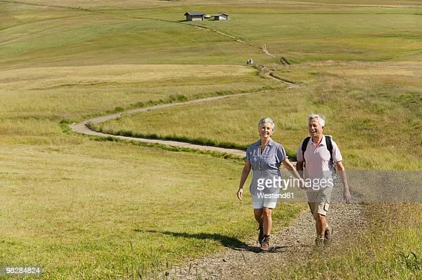 Italy, Seiseralm, Senior couple hiking, holding hands