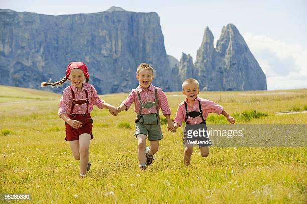 italy, seiseralm, three children (4-5), (6-7), (8-9) running in field - レーダーホーゼン ストックフォトと画像