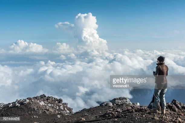 Italy, Sicily, hiker standing on Mount Etna looking at view