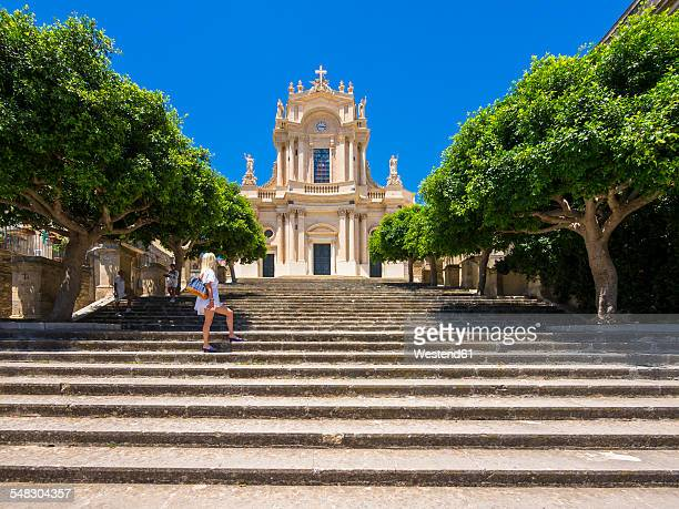 Italy, Sicily, Modica, Woman looking at San Giovanni church, UNESCO World heritage site