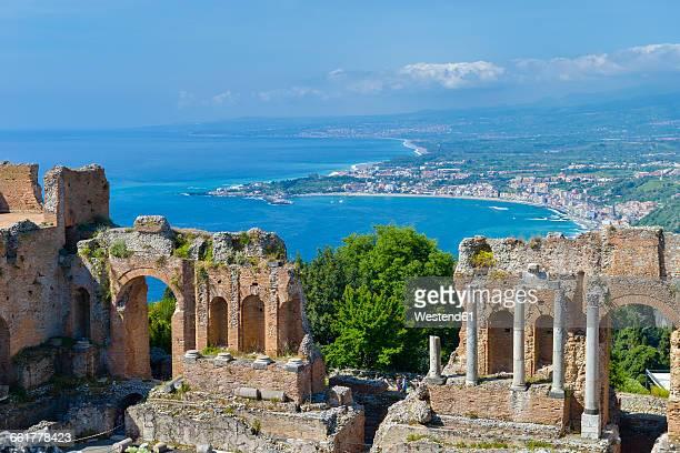 italy, sicily, taormina, teatro greco with giardini naxos in background - taormina stock pictures, royalty-free photos & images