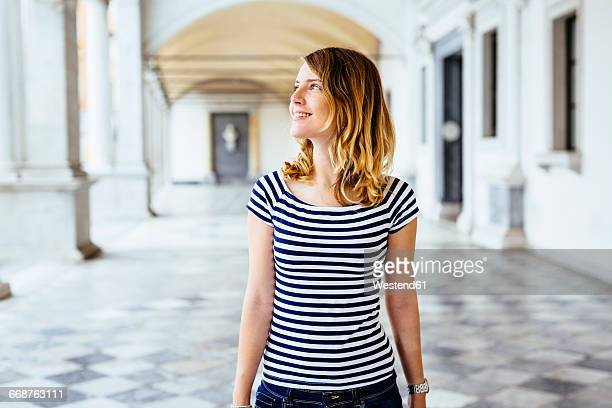 Italy, smiling young woman watching something