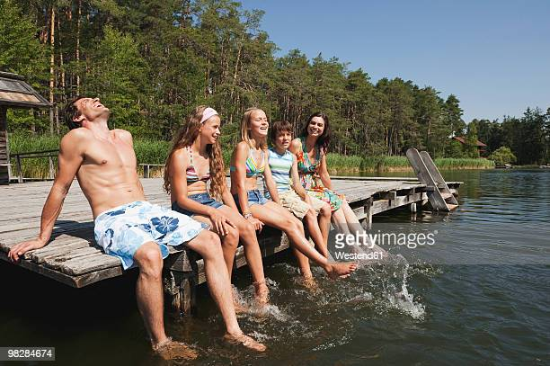 italy, south tyrol, family sitting on jetty, relaxing - fille de 12 ans photos et images de collection