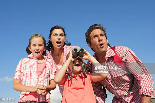 Italy, South Tyrol, Family with children (6-7) (10-11), girl looking through binoculars, portrait