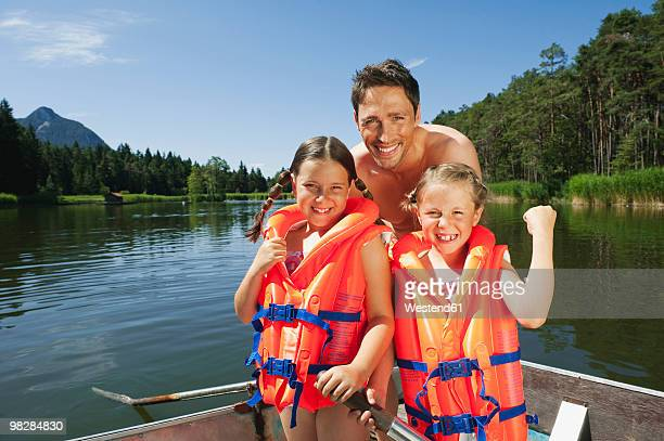 Italy, South Tyrol, Father and children (6-9), children wearing life jackets, smiling, portrait