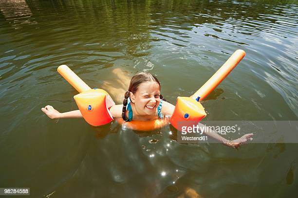 Italy, South Tyrol, Girl (8-9) swimming in lake, smiling, portrait