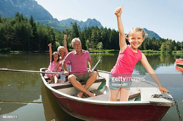 Italy, South Tyrol, Grandparents and grandchildren (6-9) sitting in rowing boat with thumbs up