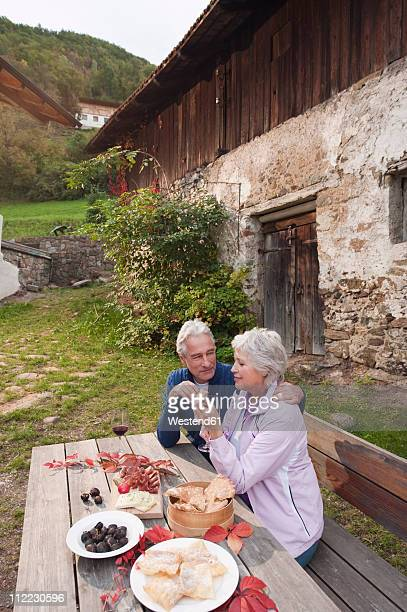 Italy, South Tyrol, Mature couple talking and having their snacks at mountain hut