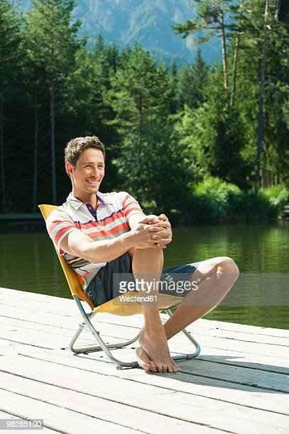 Italy, South Tyrol, Mature man sitting on chair by lake, smiling