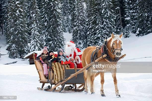 Italy, South Tyrol, Seiseralm, Santa Claus and children (6-7, 4-5, 2-3) taking sleigh ride