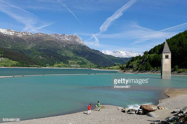 Italy, South Tyrol, Vinschgau, Old church tower of Graun in the Reschensee Lake, Two children