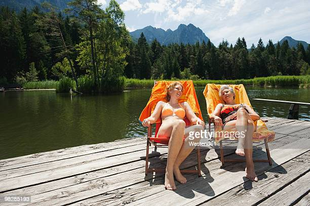 italy, south tyrol, women sitting in deck chair on jetty, smiling, portrait - women sunbathing stock photos and pictures