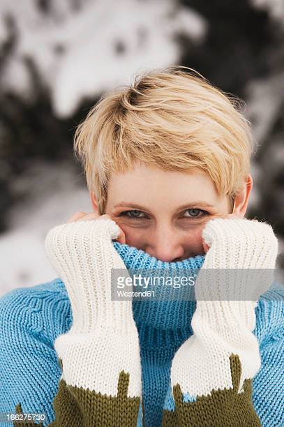 Italy, South Tyrol, Happy mature woman covering face with turtleneck pullover
