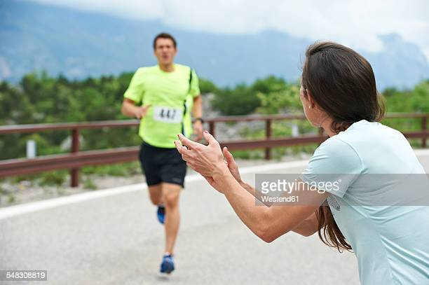 Italy, Trentino, woman rooting for runner in a competition near Lake Garda