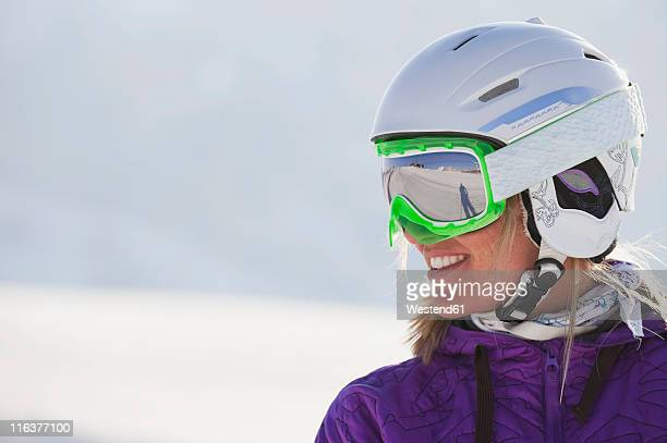 Italy, Trentino-Alto Adige, Alto Adige, Bolzano, Seiser Alm, Young woman wearing skiing helmet and ski goggles, smiling, close up
