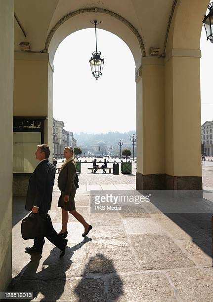 Italy, Turin, Business couple walk through porticos in front of piazza
