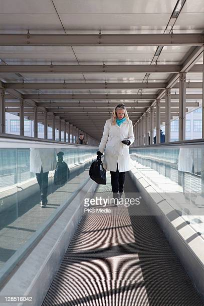 Italy, Turin, Woman checking text message on moving walkway