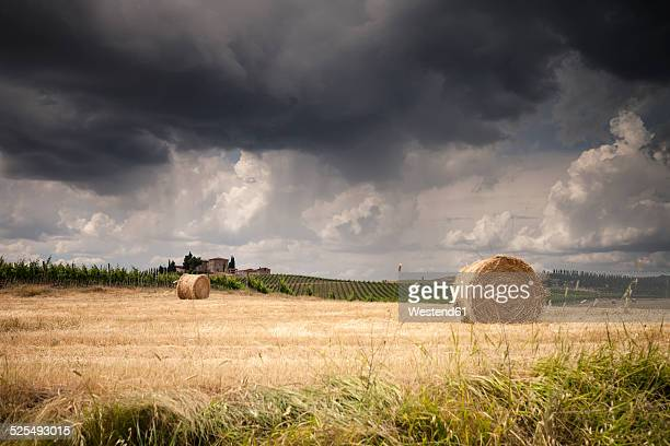 Italy, Tuscany, Chianti, Tuscan landscape with haybales at upcoming thunderstorm