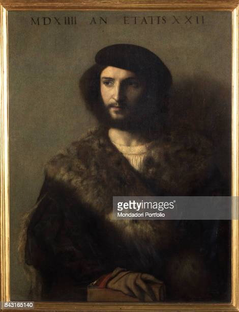 Italy Tuscany Florence Galleria degli Uffizi Whole artwork view Young man with pale skin and face framed by hair and thick beard wearing dark hat...