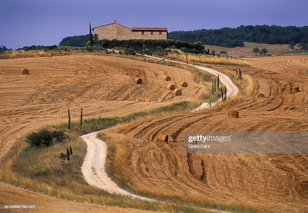 Italy, Tuscany, hay bales in fields near farmhouse : Stockfoto