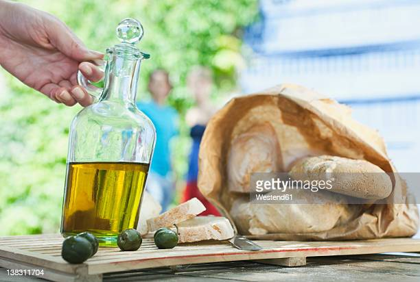 italy, tuscany, magliano, close up of bread, olive oil and olives on wooden table - cruet stock photos and pictures
