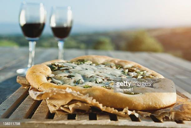 Italy, Tuscany, Magliano, Close up of pizza with wine glasses