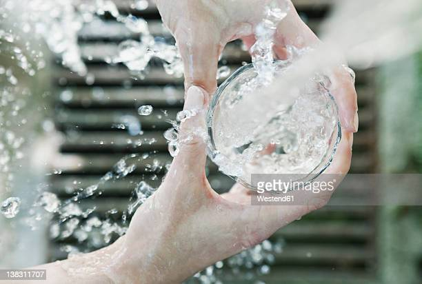 italy, tuscany, magliano, close up of woman's hand filling water glass - trinkwasser stock-fotos und bilder