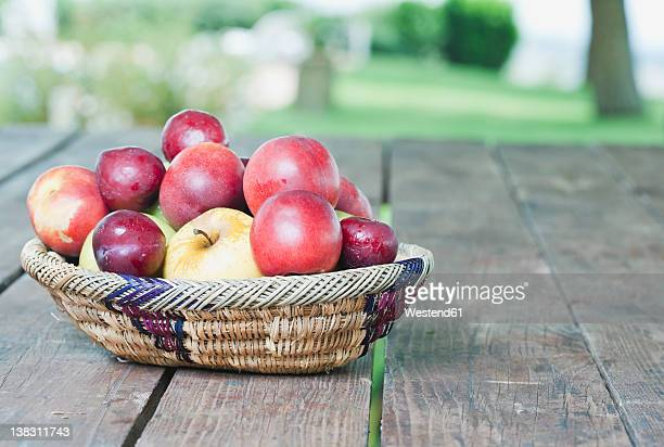 italy, tuscany, magliano, fruit basket with apples and plums on wooden table - ciruela fotografías e imágenes de stock
