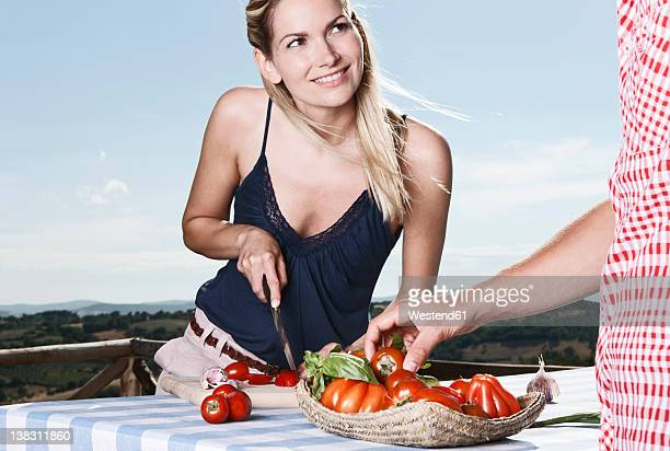Italy, Tuscany, Magliano, Young man standing near table and woman cutting tomatoes, smiling