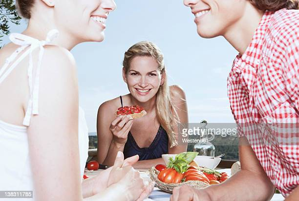 Italy, Tuscany, Magliano, Young woman holding food and friends in foreground, smiling