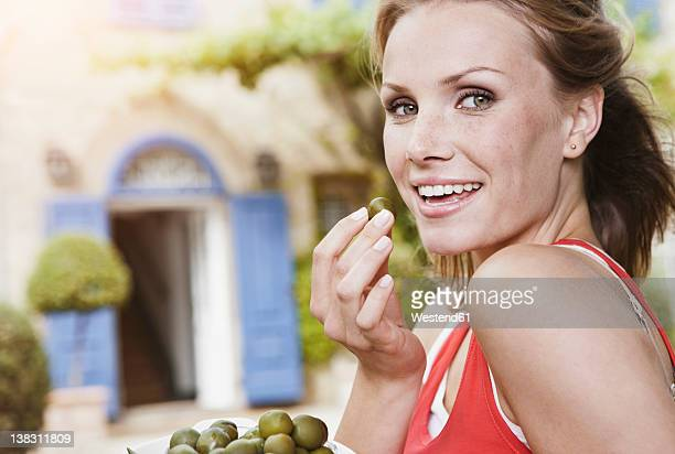 Italy, Tuscany, Magliano, Young woman holding green olives, smiling, portrait