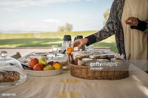 Italy, Tuscany, Maremma, woman at laid breakfast table on terrace