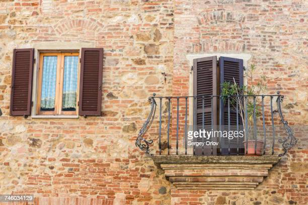 Italy, Tuscany, Montepulciano, Stony and brick facade of house with carved metal balcony and latticed sun blinds