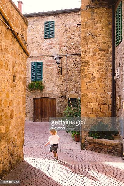 Italy, Tuscany, Pienza, Little girl running through lane in historic old town