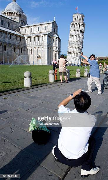 Italy Tuscany Pisa tourist taking a photograph of another man pretending to hold up the Leaning Tower of Pisa in The Campo dei Miracoli or Field of...