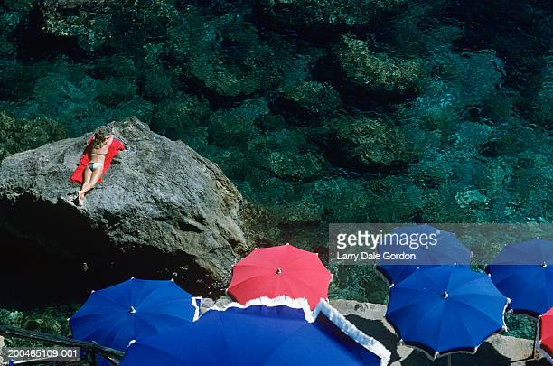 Italy, Tuscany, Porto Ercole, woman sunbathing on rock, elevated view