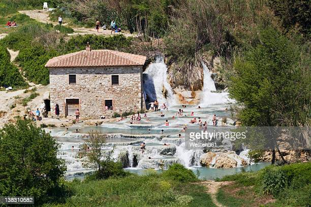 Italy, Tuscany, Province of Grosseto, Saturnia, View of people at thermal waterfalls and travertine pool