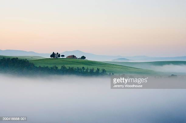 Italy, Tuscany, San Quirico d'Orcia, mist in valley, dawn