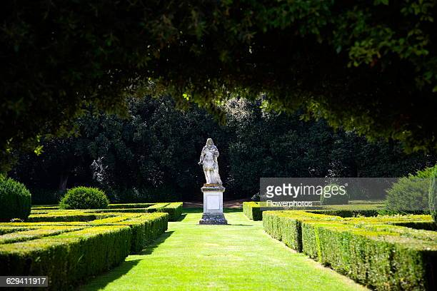 Italy, Tuscany, San Quirico, Val D'Orcia, The 16th Century Horti Leonini formal gardens by Diomede Leoni with view along grass pathway lined by...