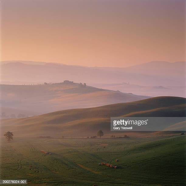 italy, tuscany, siena, val d'orcia hay bales in field at sunrise - yeowell stock pictures, royalty-free photos & images