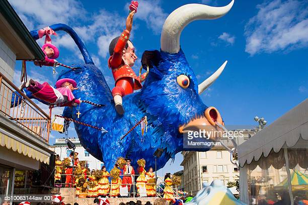 Italy, Tuscany, Versilia, Viareggio, People wearing carnival mask, low angle view