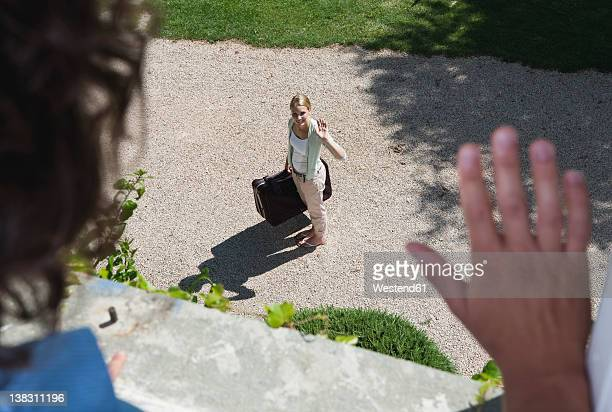 Italy, Tuscany, View of young woman with luggage from hotel window