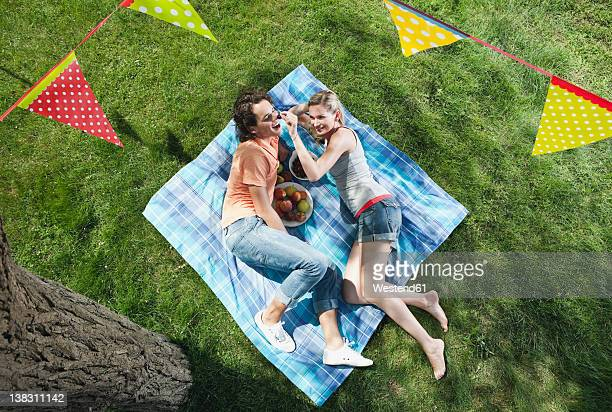 Italy, Tuscany, Young couple lying on picnic blanket with food and flag line hanging above